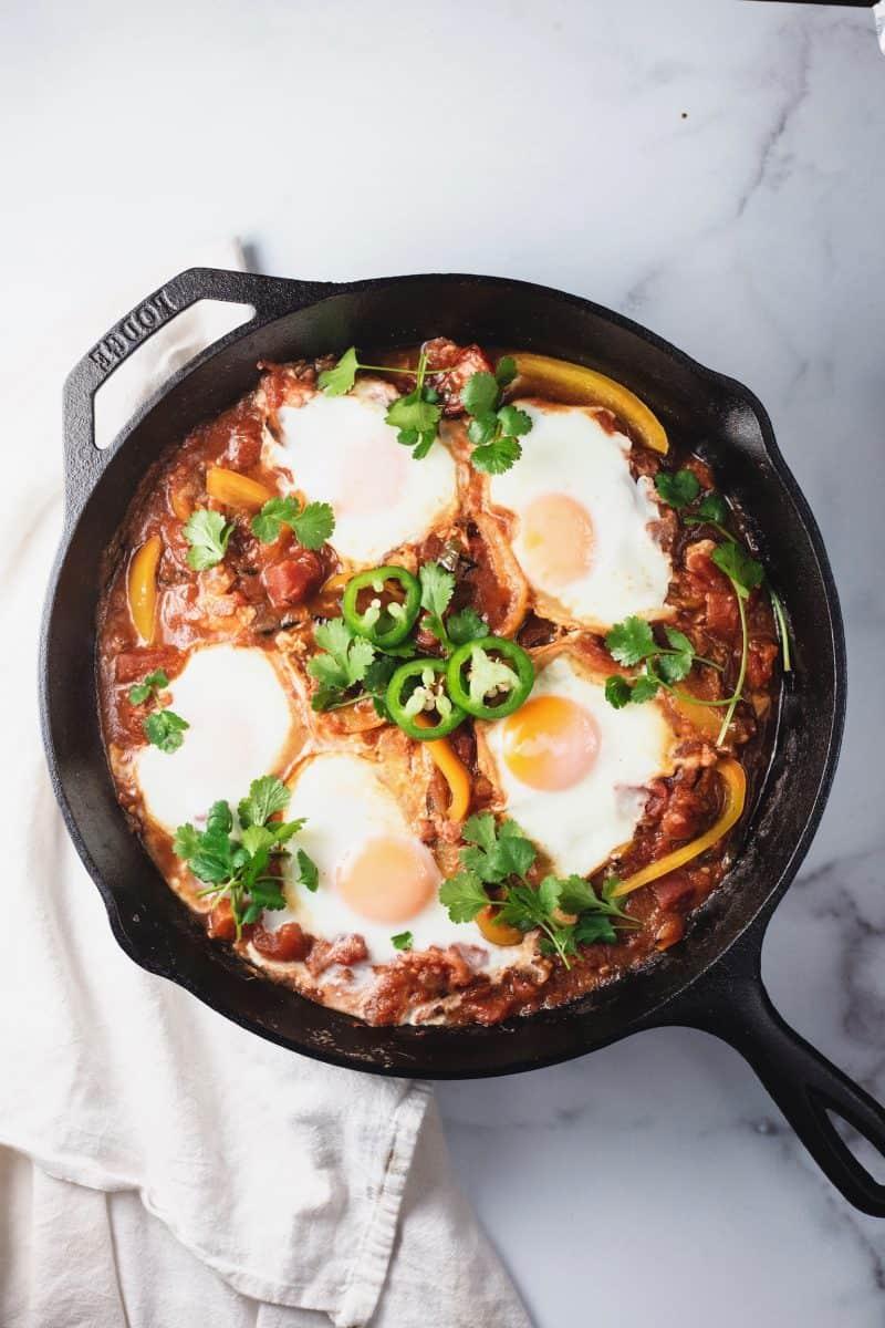 Over head shot of Shakshuka recipe with eggs and jalapeño