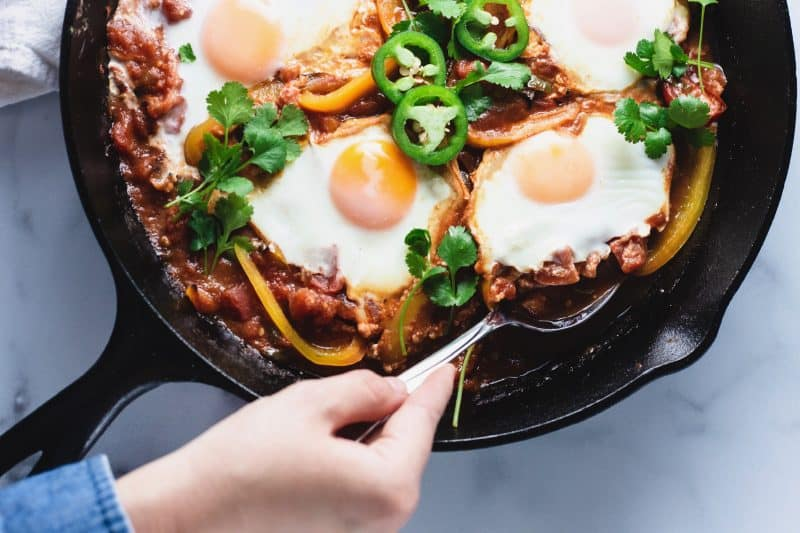 Close up shot of spoon scooping poached egg out of shakshuka recipe