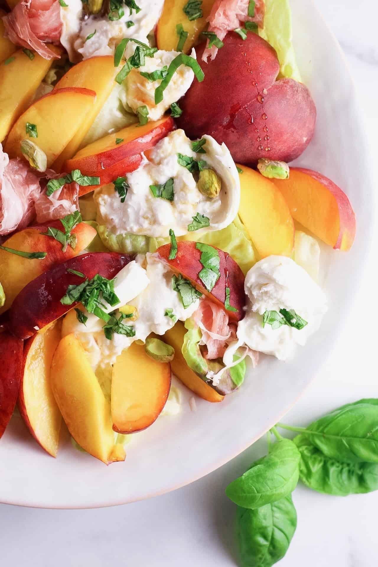 Close up shot of ripe peaches with burrata cheese, pistachio and prosciutto
