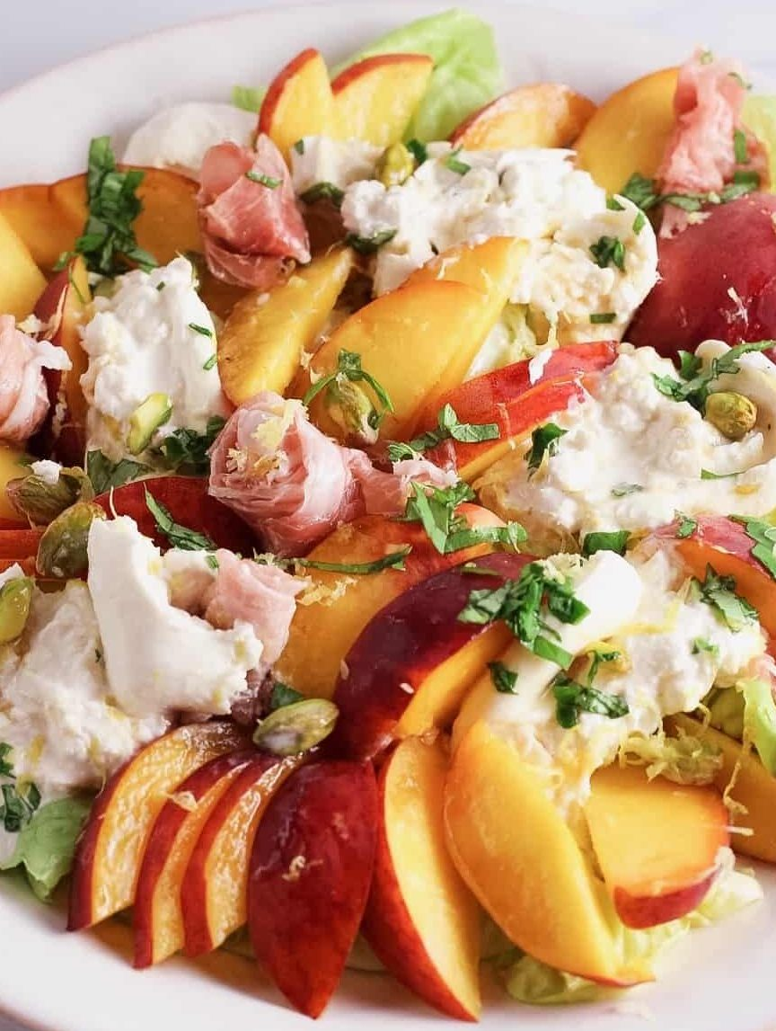 Close-up of fresh peaches with prosciutto, basil and burrata cheese
