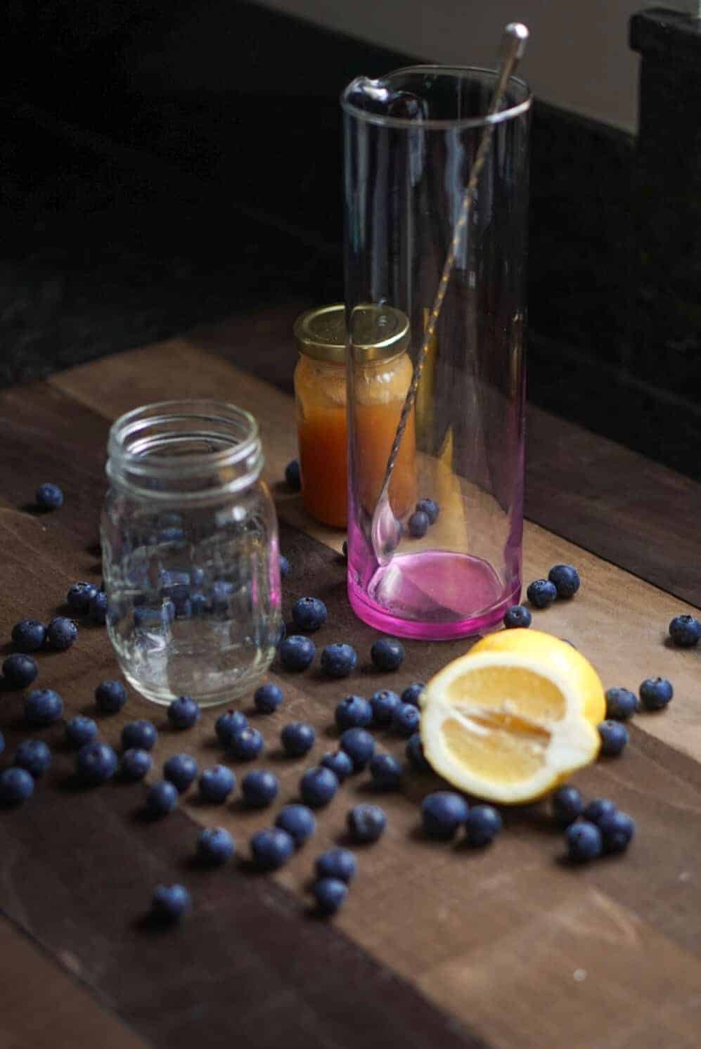 deconstructed lemonade with scattered blueberries, a lemon wedge and glassware