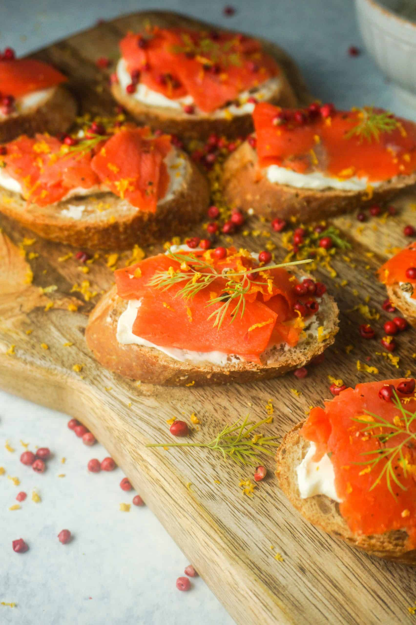 Close up of smoked salmon on wooden board with lemon and pink peppercorns