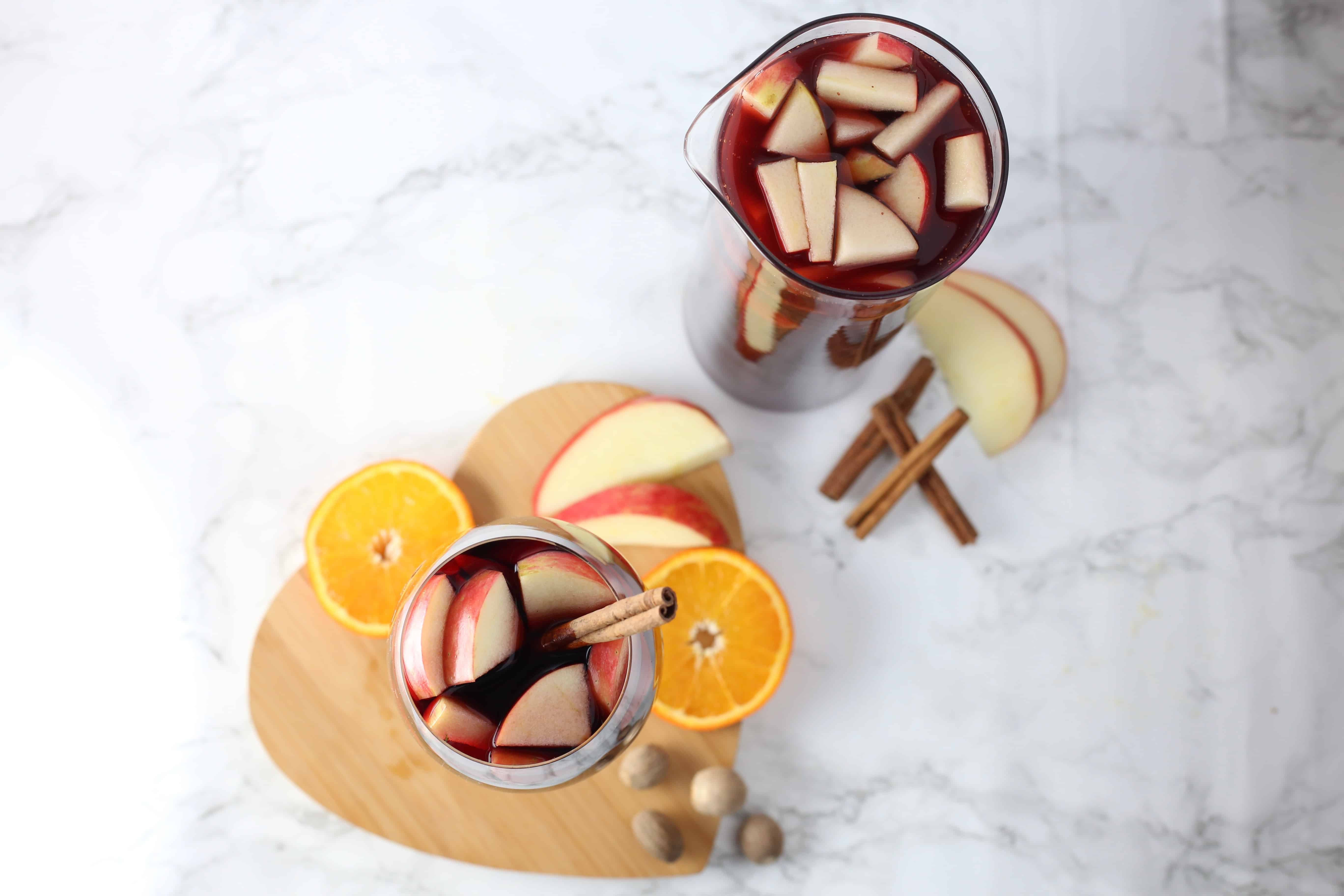 Two glasses shot overhear with wine, apples, spices and orange