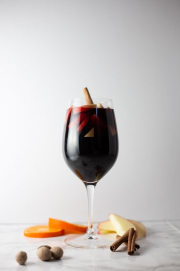 Wine glass with sangria, apples, orange, and nutmeg