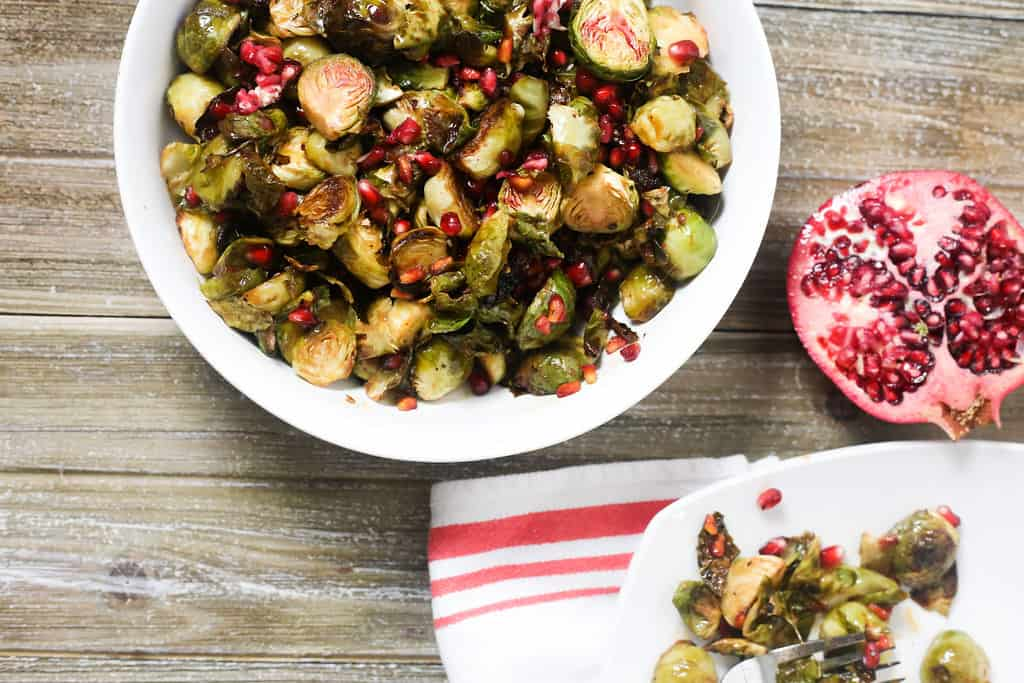 Roasted Brussels sprouts in a bowl with pomegranate seeds next to pomegranate and plate of brussels sprouts