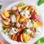 Overhead flatay of fresh peach, nectarine, basil and burrata salad