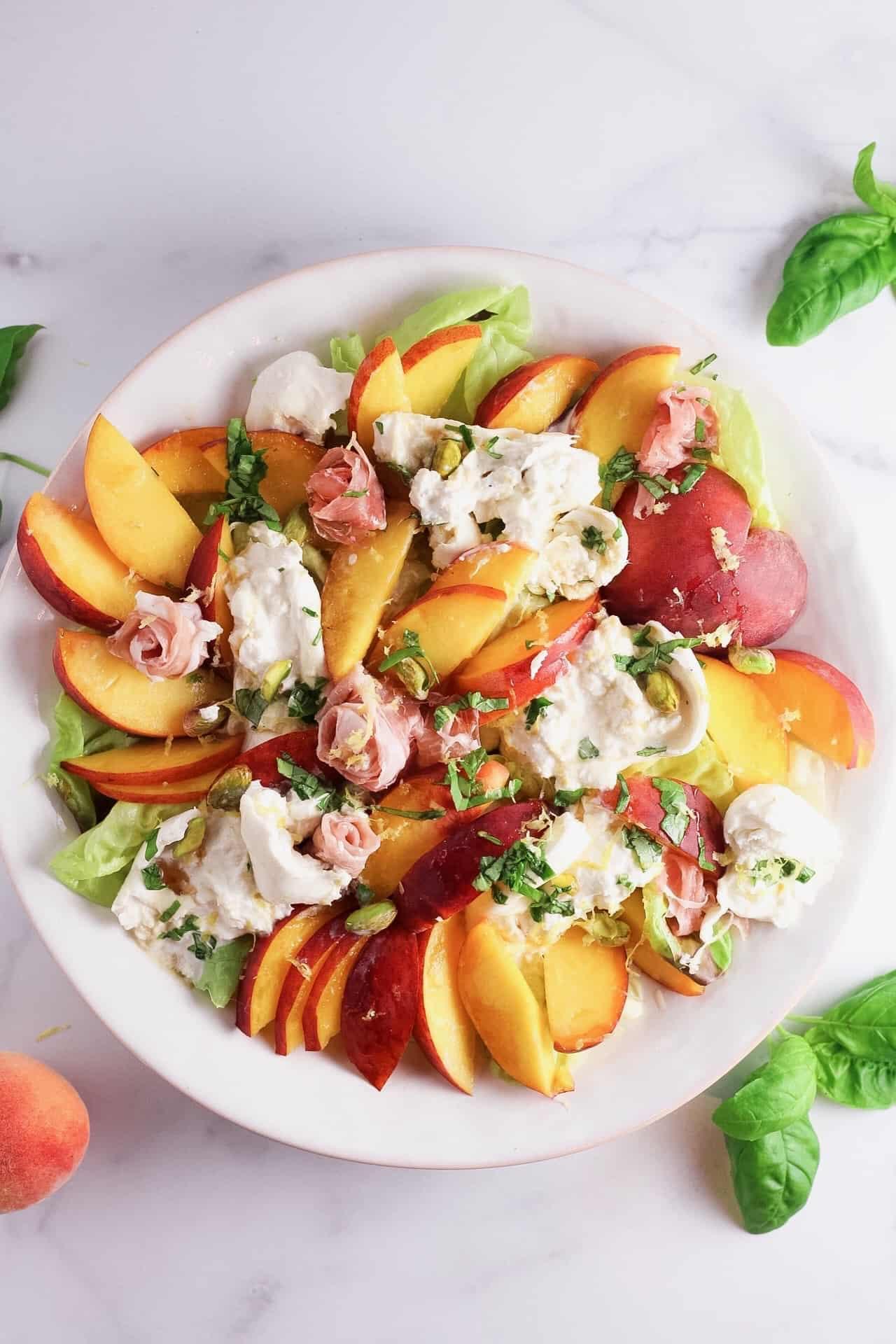 Overhead flatay of fresh peach, nectarine, basil and burrata salad
