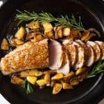 pork tenderloin in cast iron pan with apples and fresh herbs