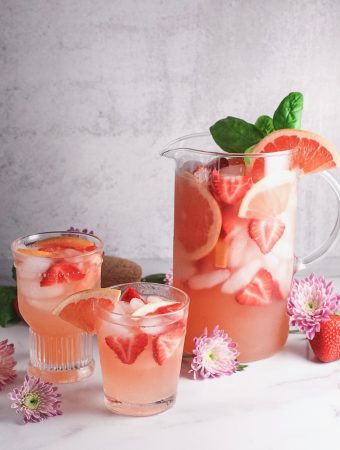 Pitcher and two glasses of fresh grapefruit and strawberry sangria