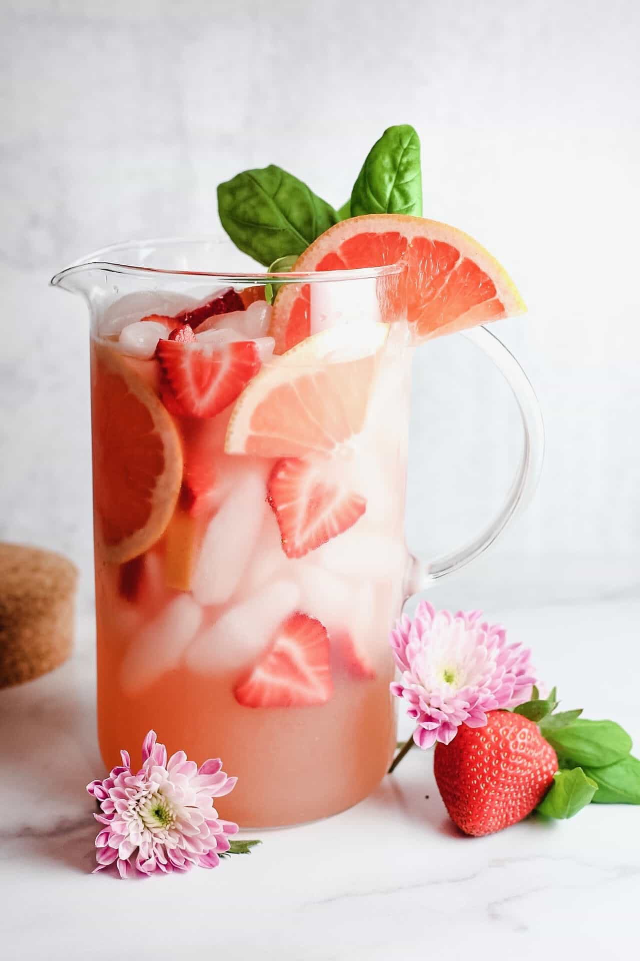 Pitcher of white sangria with grapefruit and strawberries