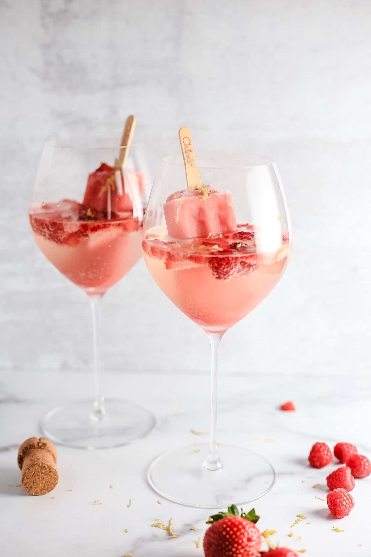 Two large wine glasses filled with prosecco, berries and strawberry popsicles