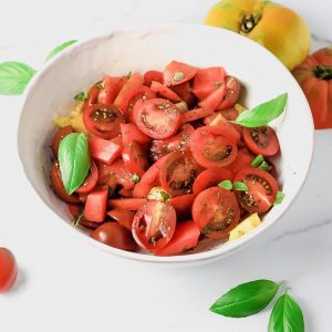 Bowl of fresh cherry and heirloom tomatoes with basil