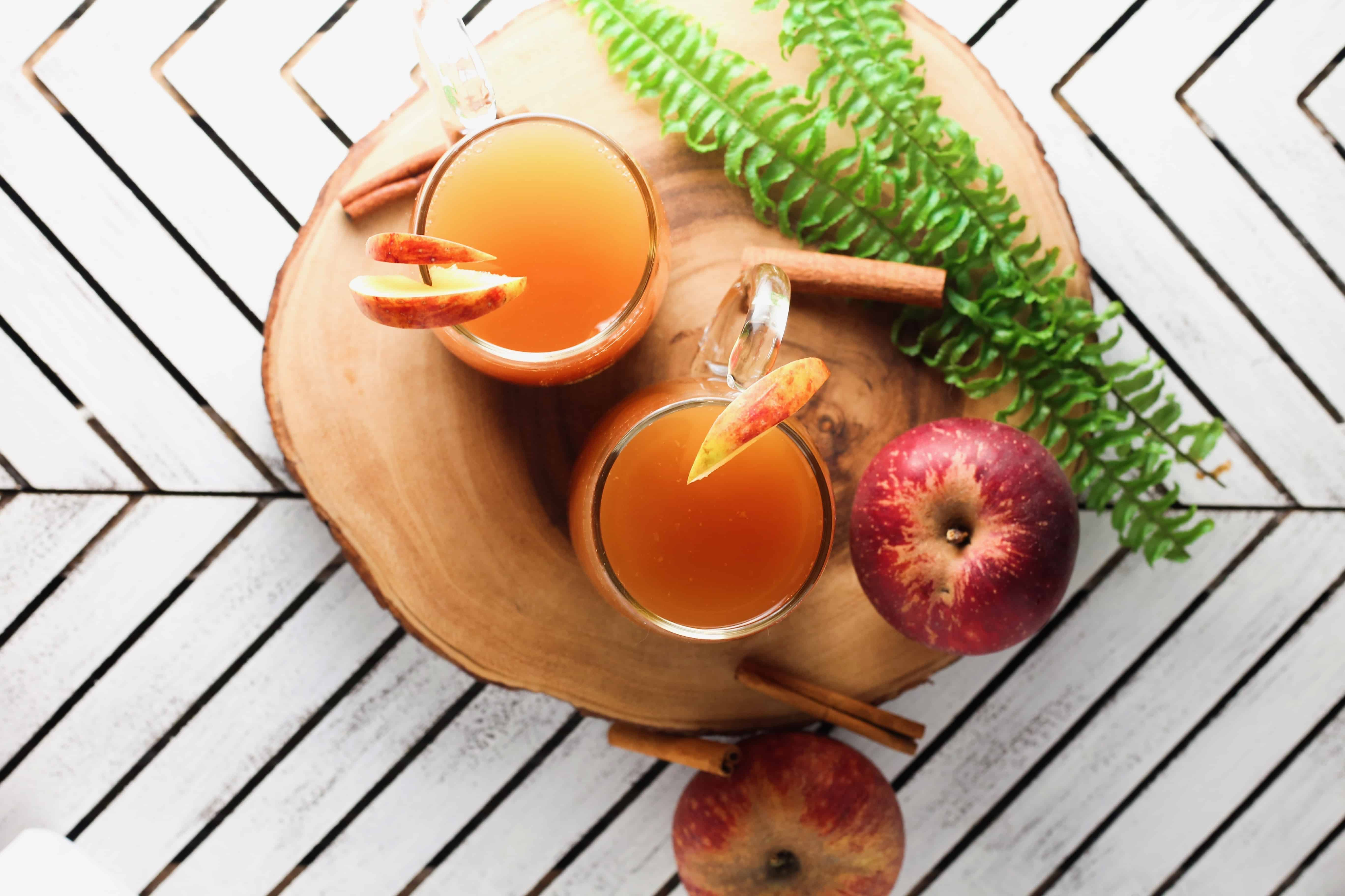 Overhead flatlay of two mugs with spiked apple cider, a fern, an apple and cinnamon sticks