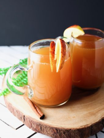 Two glasses on a wood board with cinnamon, bourbon and apple cider