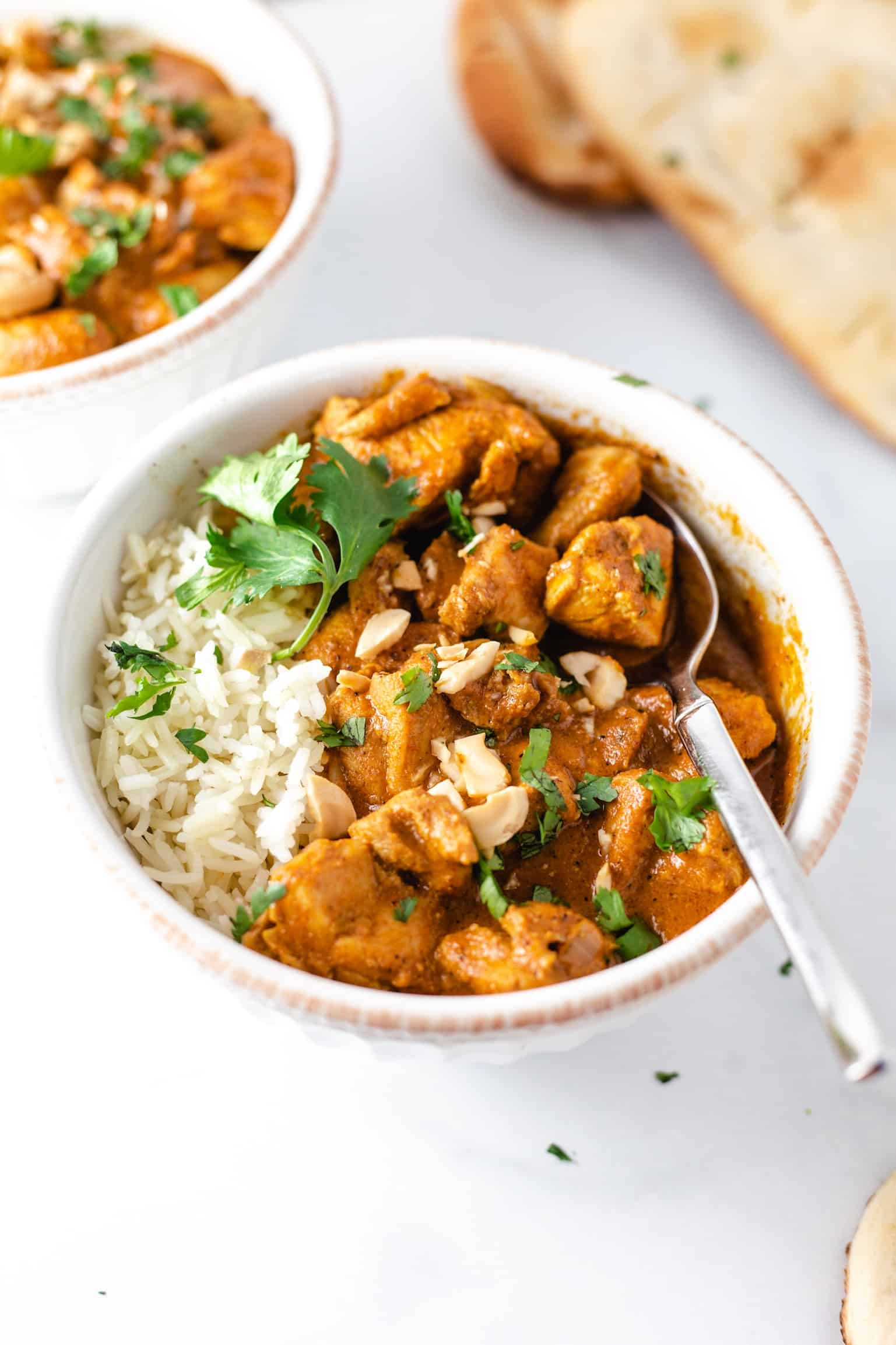 Bowl of butter chicken with jasmine rice, cashews and cilantro with a spoon