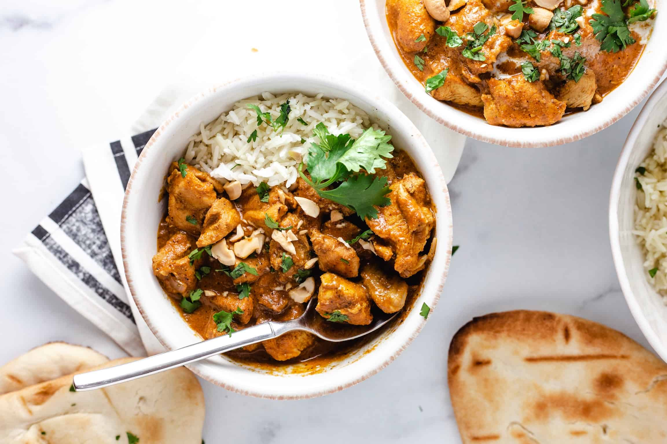 Two bowls of butter chicken with naan, fresh cilantro and cashews