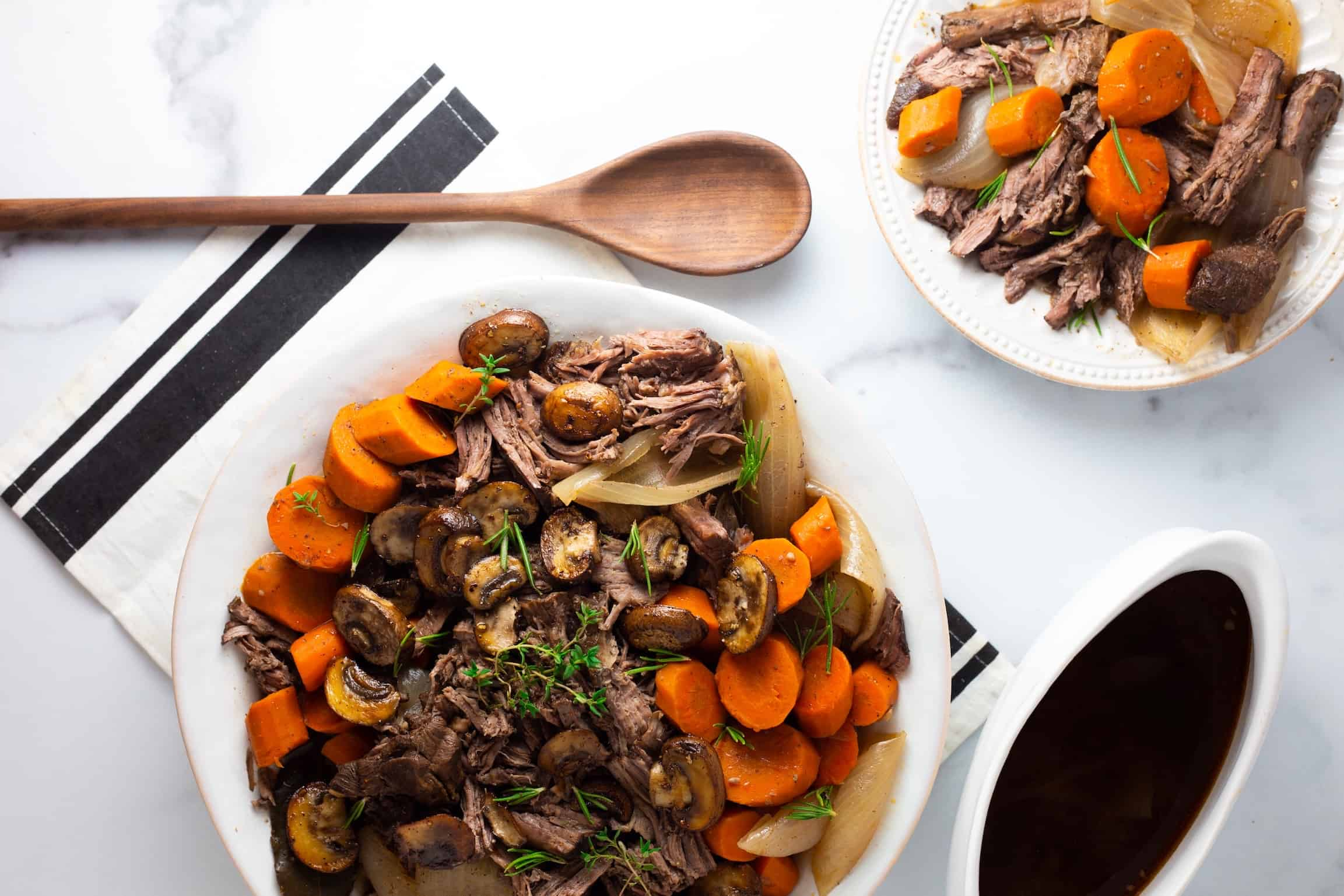 Serving platter and plate with pot roast and carrots with wooden spoon and au jus