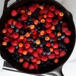 Raw berries for berry crumble in cast iron pan