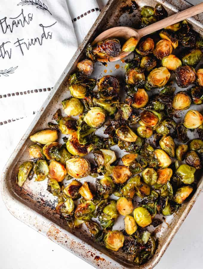 Brussels sprouts on a sheet pan with orange over a napkin