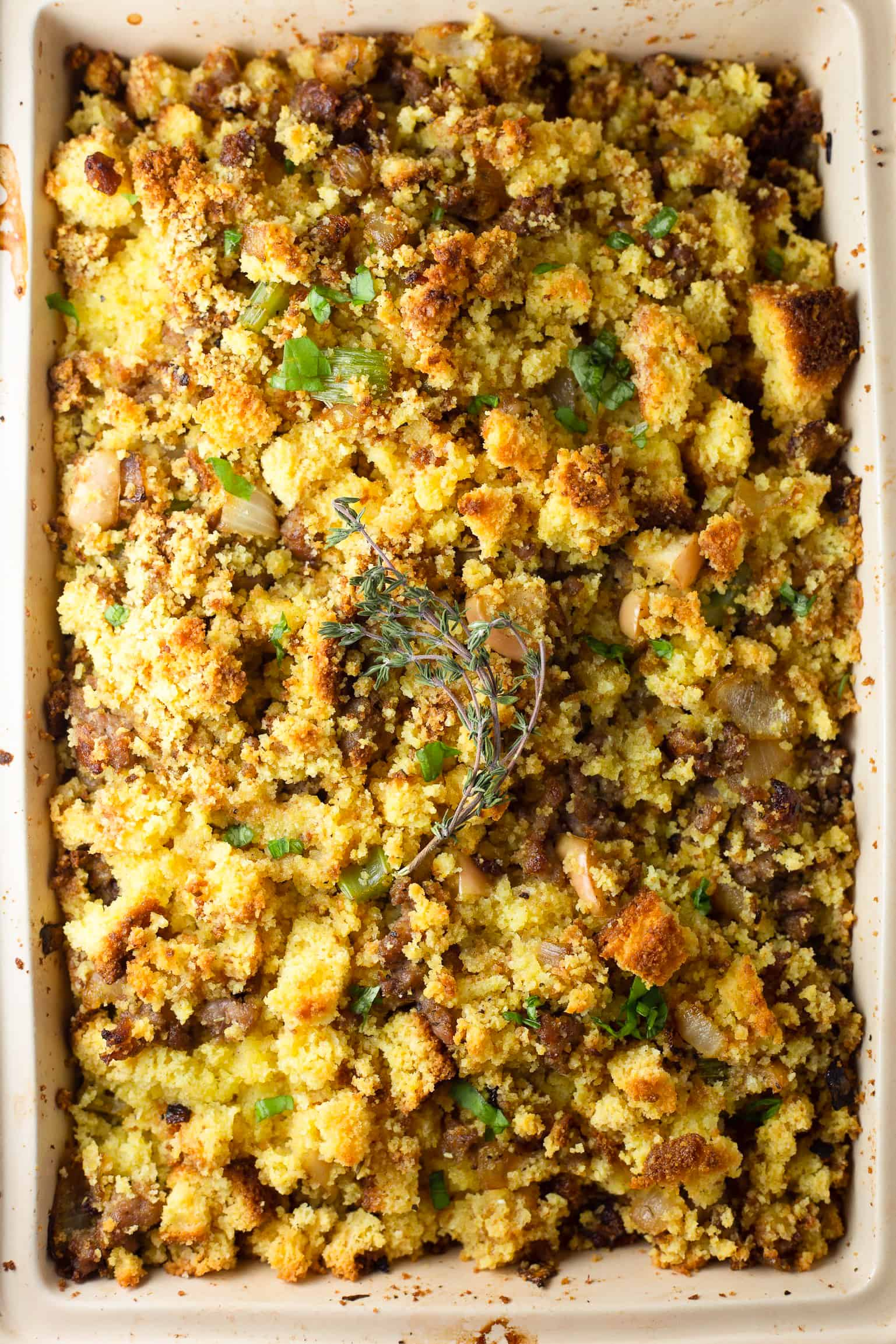 Baking dish with cornbread, sausage, apple, thyme and parsley