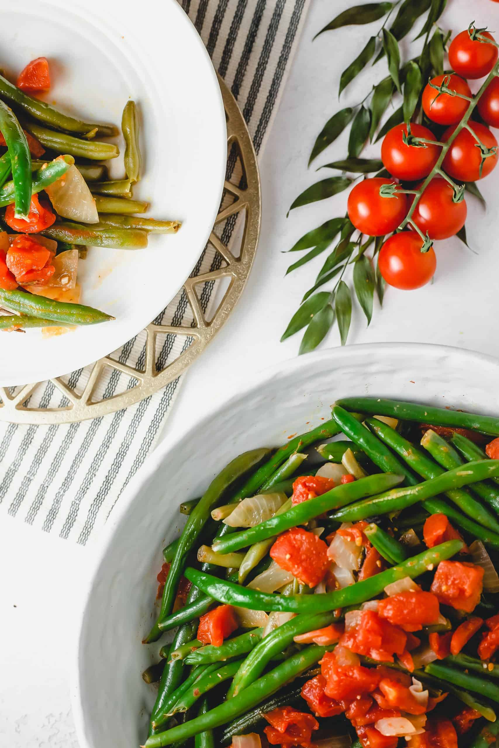 Large bowl and plate with green bean recipe, napkin and fresh tomatoes