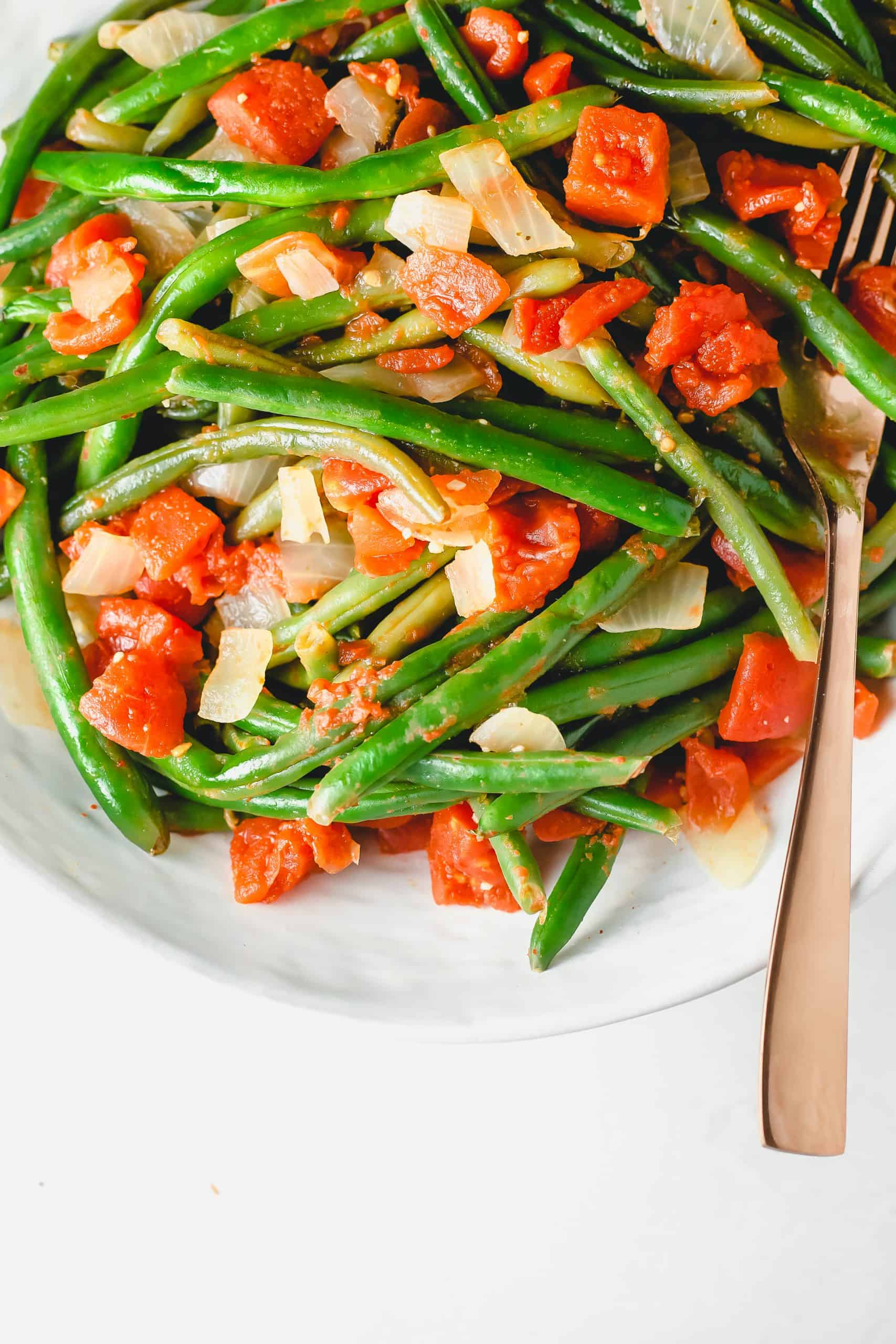 Close up of cooked green beans with tomato and onion