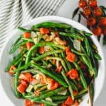 Bowl of cooked green beans with tomatoes and onion