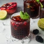 Pomegranate cocktail in a bucket glass with mint and ice