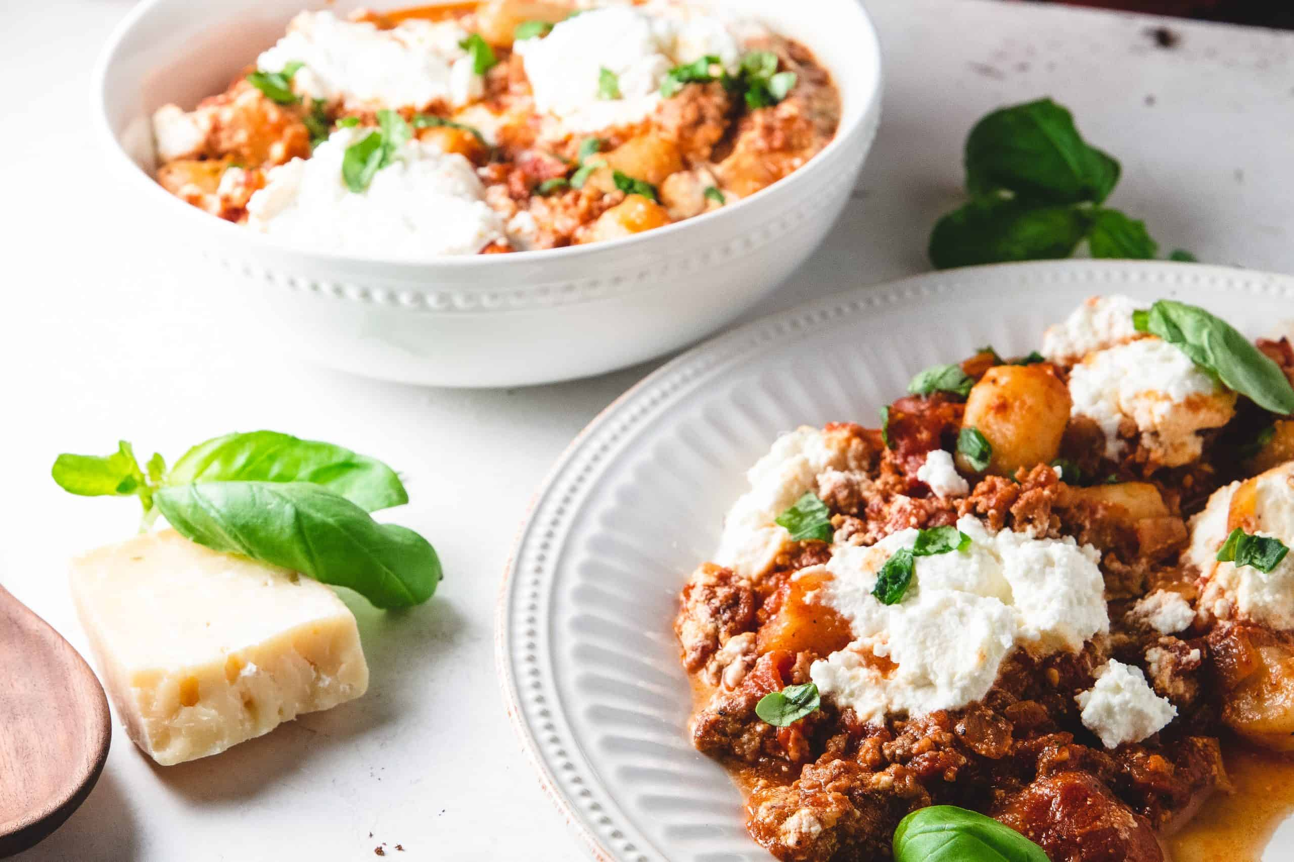 Plate and Bowl of pasta with parmesan cheese, basil and ricotta