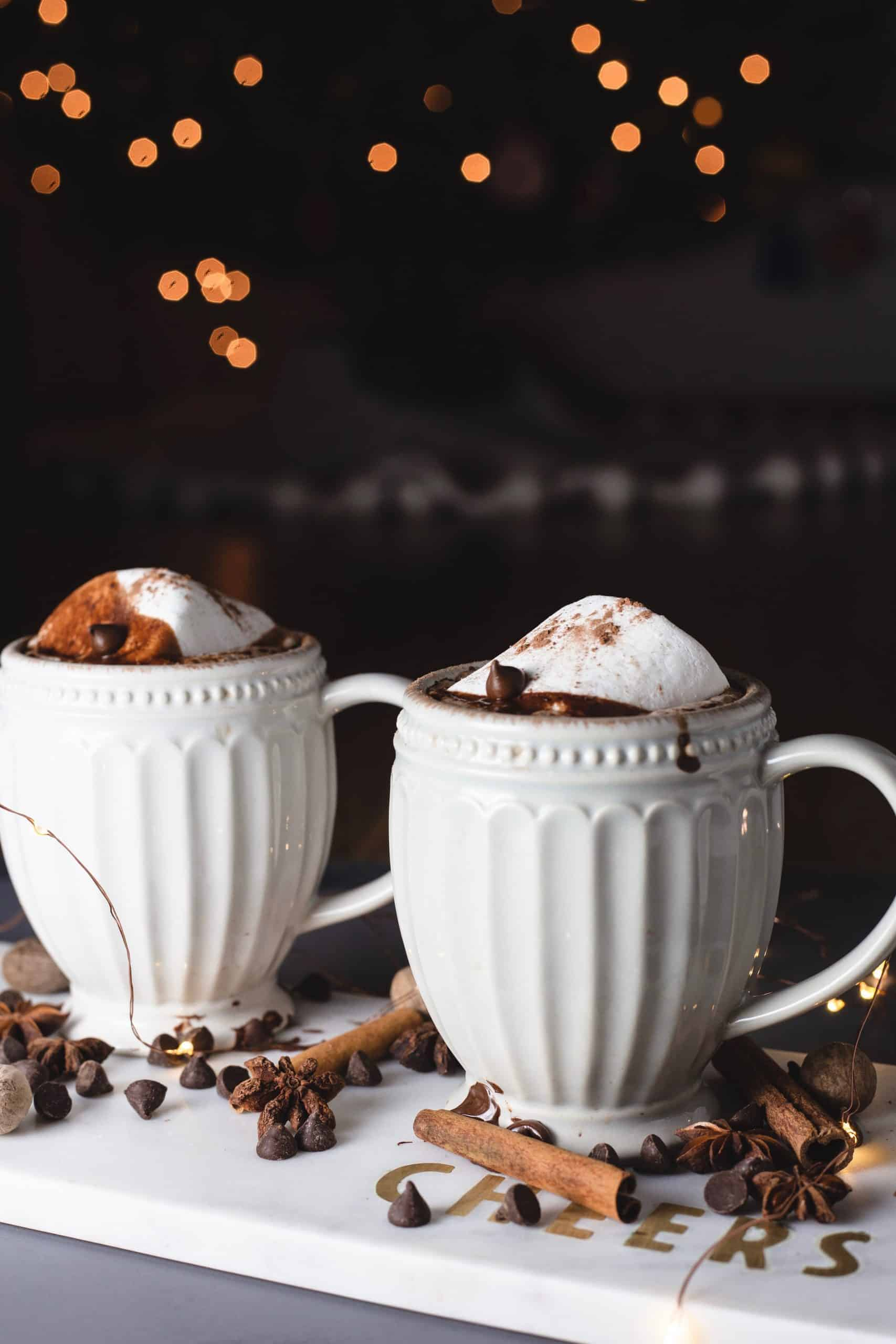 Two mugs with hot chocolate and chocolate dripping down the side with string lights