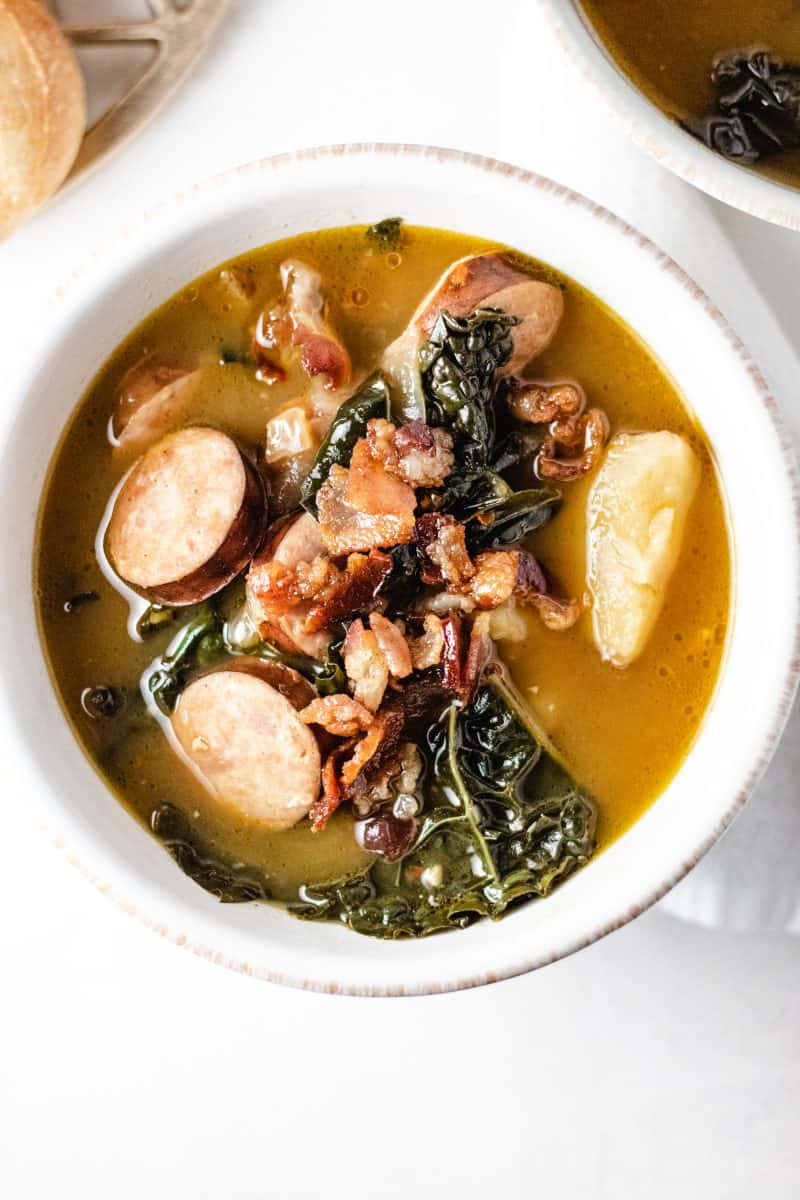 Soup with kale potato and bacon in white bowl on napkin