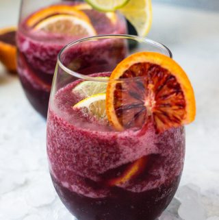 Two wine glasses with sangria and fresh fruit over crushed ice
