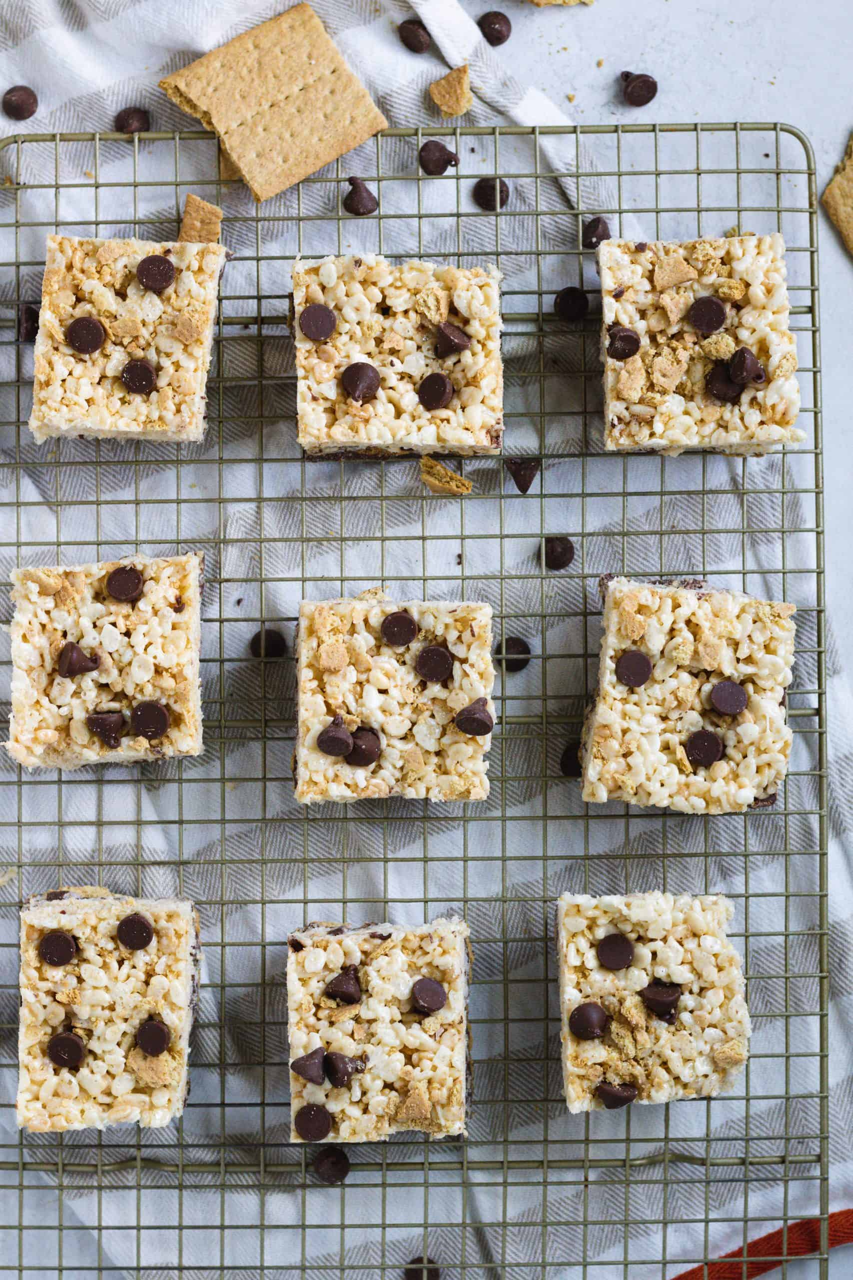 Baking rack with rice krispies, chocolate chips and graham cracker over kitchen towel
