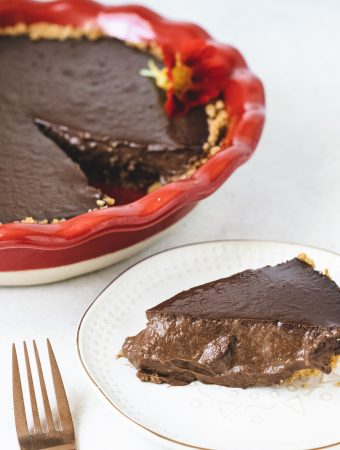 Chocolate pie in pie dish next to a slice on a plate with gold fork