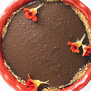 Chocolate pie in red pie dish with edible flowers