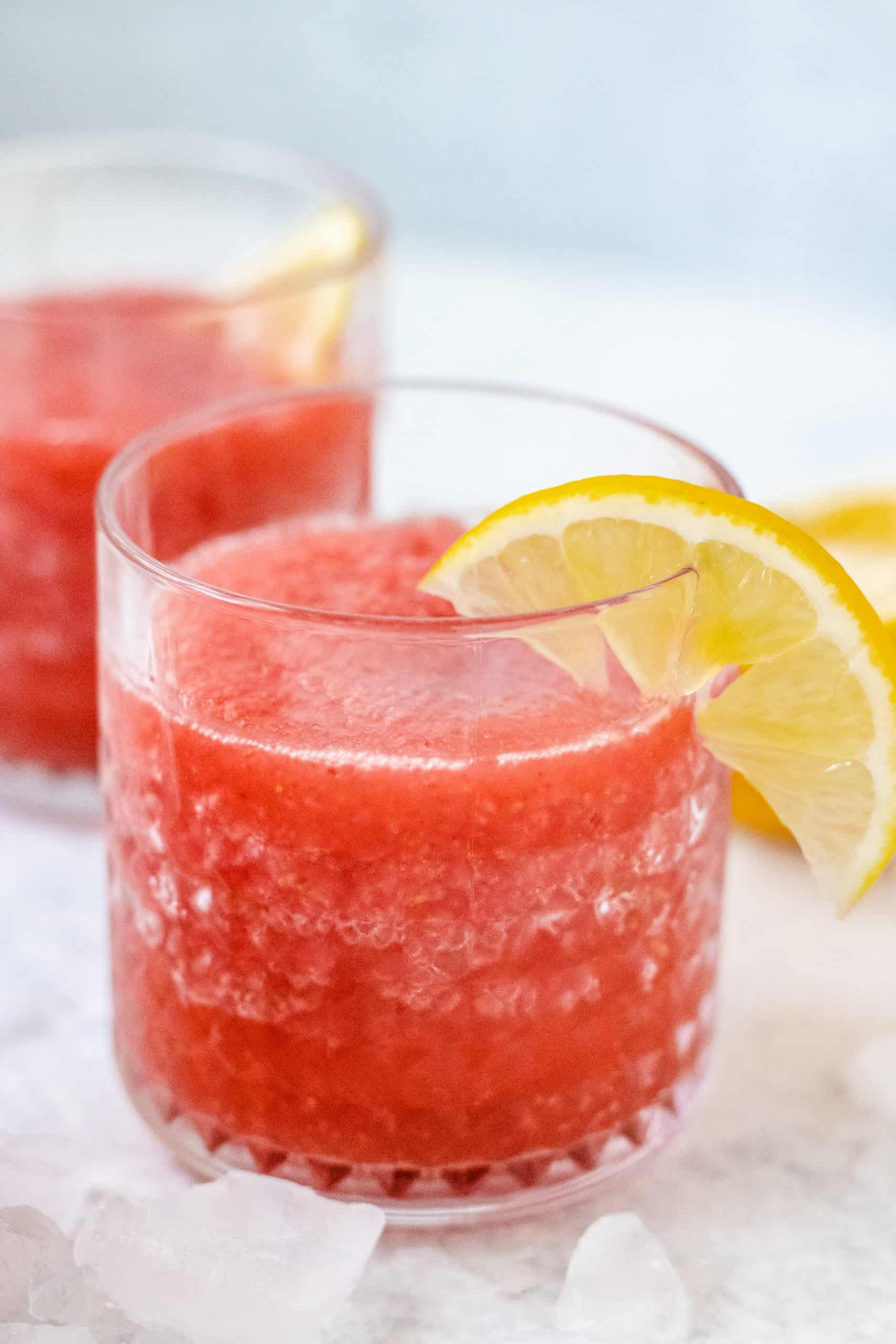Two bucket glasses with strawberry slushie with lemon and ice